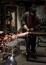 Sparks shooting away from where the grinder meets the metal